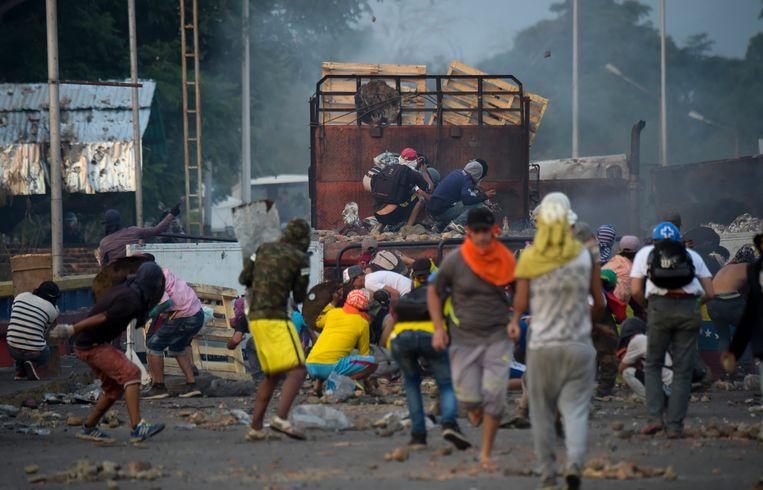 Aanhangers van de zelfbenoemde interim-president Juan Guaidó strijden afgelopen weekend met troepen van president Nicolás Maduro op de grensbrug Francisco de Paula tussen Colombia en Venezuela. Beeld AFP