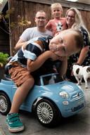 Bram zit op een speelgoedauto met op de achtergrond zijn ouders Marianne en Ronald Vreeswijk en zusje Lieke.
