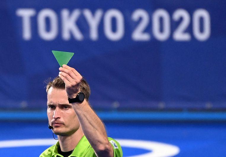 De hockeyscheidsrechter haalde ook de voorbije wedstrijden op de Spelen al geregeld zijn groene 'driehoek' boven, goed voor twee minuten straftijd. Beeld AFP