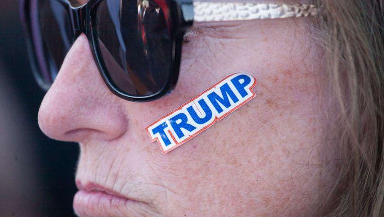 Een vrouwelijke aanhanger van Donald Trump met een sticker op haar gezicht. Beeld AFP