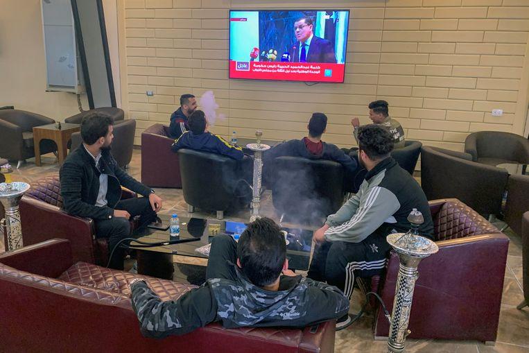 Met een waterpijp in de hand volgen Libiërs de persconferentie op televisie.   Beeld Reuters