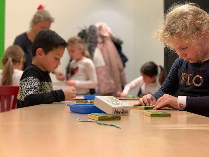 Kinderen werken tijdens de workshop Pakje Kunst Take Over geconcentreerd aan hun kunstwerk.