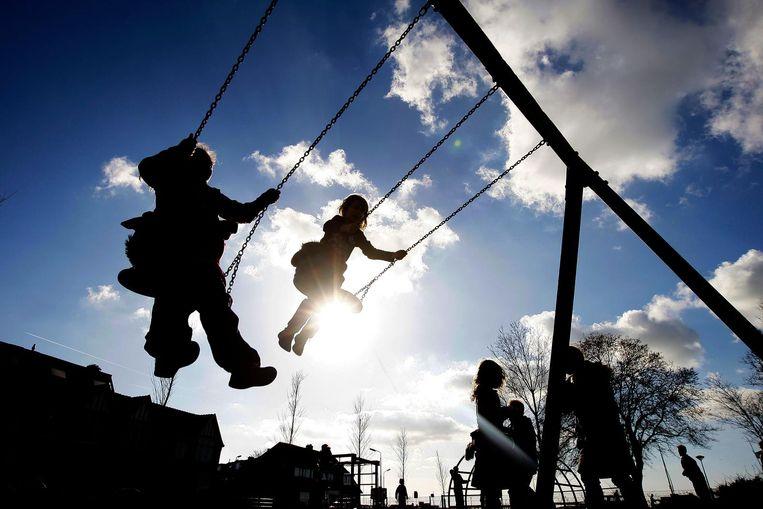 Kinderen schommelen in een speeltuintje in IJmuiden. Beeld anp