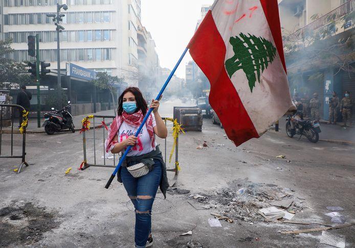 Une manifestante porte un drapeau national le long d'une route bloquée, lors d'une manifestation contre la chute de la livre libanaise et les difficultés économiques croissantes, près du bâtiment de la Banque centrale, à Beyrouth, Liban, le 16 mars 2021.