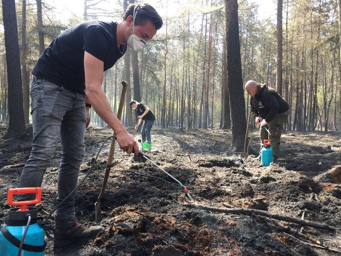 Dolf van Beers (links) helpt samen met andere vrijwilligers met nablussen op de Kerkeindse Heide