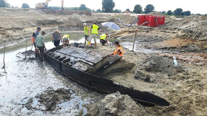 Archeologen en vrijwilligers zijn druk in de weer met het opgraven van een platbodem.
