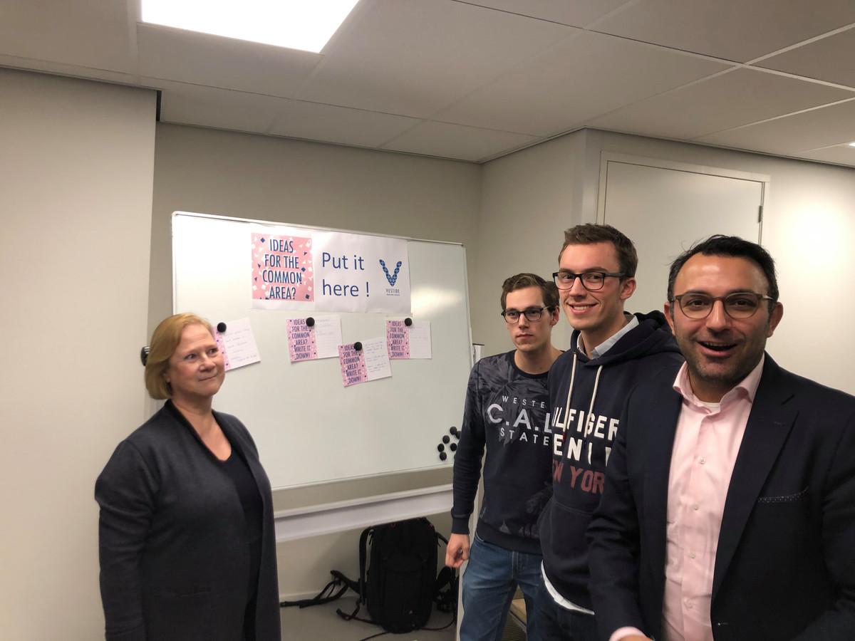 Directeur Ingrid de Boer van Woonbedrijf (links) en wethouder Yasin Torunoglu (rechts) met twee studentbeheerders van het complex tijdelijke studentenwoningen op het Slachthuisterrein in Eindhoven, Mark Wolters (tweede van links) en Sjoerd Hutter.