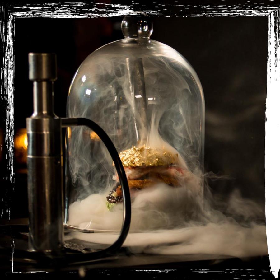 """Le burger """"Golden Boy"""", présenté sur une ardoise et sous cloche, est servi dans une fumée infusée de whisky"""