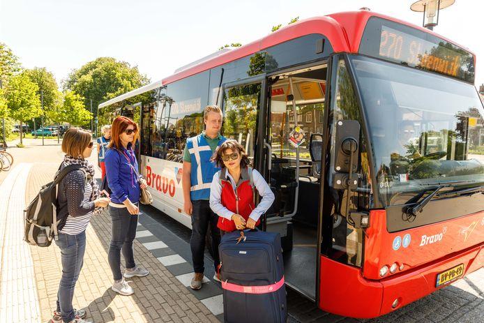 Stagaires helpen Aziatische toeristen de nieuwe Giethoorn Express in.