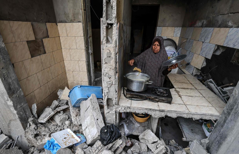 Een Palestijnse vrouw maakt het eten klaar in wat overblijft van haar huis in Gaza-stad. Beeld AFP