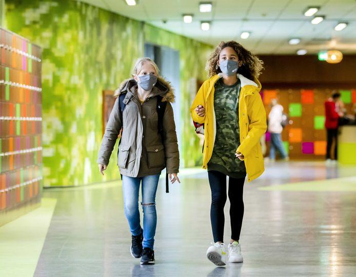 Leerlingen van een middelbare school dragen mondkapjes in de gang.