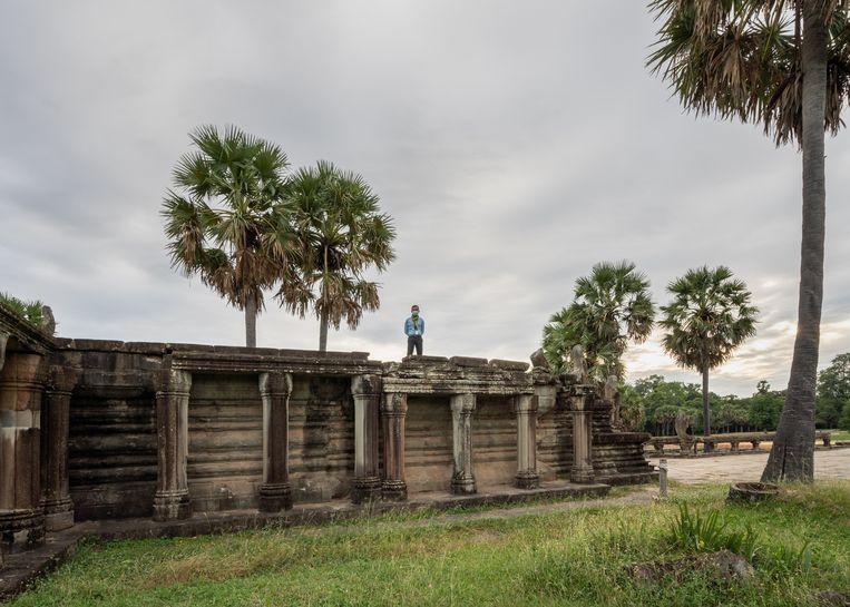Bewaker in de behuizing van het lege tempelcomplex van Angkor Wat. Met de covid 19-crisis heeft het jaar 2020 een kritieke daling gezien van het aantal bezoekers aan de normaal overvolle tempels. Beeld Antoine Raab