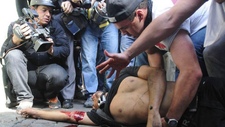 Een van de demonstranten ligt gewond op de grond. Beeld epa