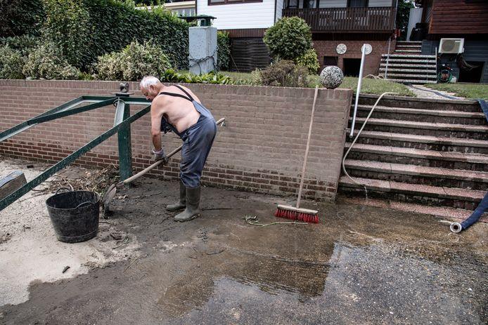 Heinz Goy is net aangekomen bij zijn vakantiechalet pal aan de Maas in Maashees. Hij maakt zijn ondergelopen kelder en achtertuin schoon.