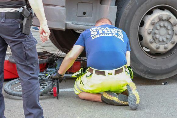 Fiets wordt van onder de vrachtwagen gehaald