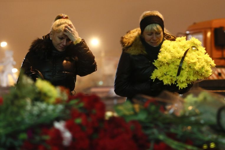 Twee vrouwen leggen bloemen nabij het treinstation waar zondag 17 mensen omkwamen. Beeld AP