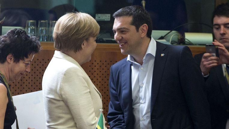 De Duitse bondskanselier Angela Merkel schudt de Griekse premier Alexis Tsipras (rechts) de hand. Beeld reuters