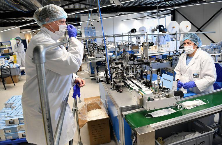 Fleur Bakker (l) van de Mondmaskerfabriek in gesprek met een medewerker over de kapjes op de productievloer. Beeld Marcel van den Bergh