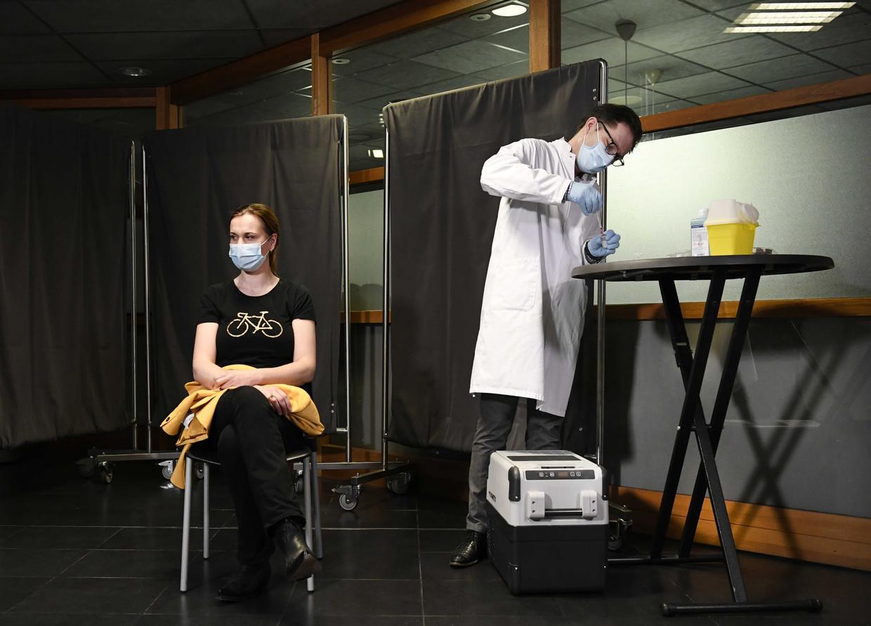 Een huisarts krijgt de eerste prik toegediend in het Medisch Spectrum Twente. In totaal 15.000 mensen komen in aanmerking voor deze vaccinatieronde. Beeld ANP