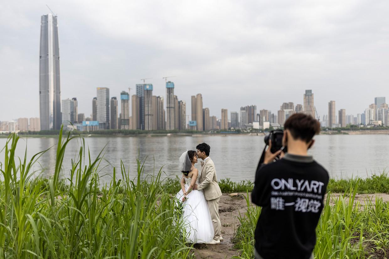 Een stel maakt huwelijksfoto's langs de Yangtzerivier in Wuhan, 8 april.    Beeld Getty