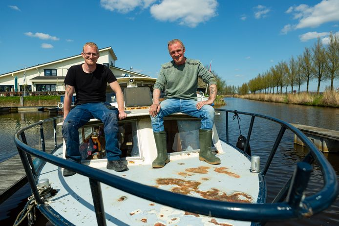 """Peter en zoon Jimmy zijn druk bezig om de pas aangeschafte boot op te knappen: ,,Het is mijn allereerste."""""""