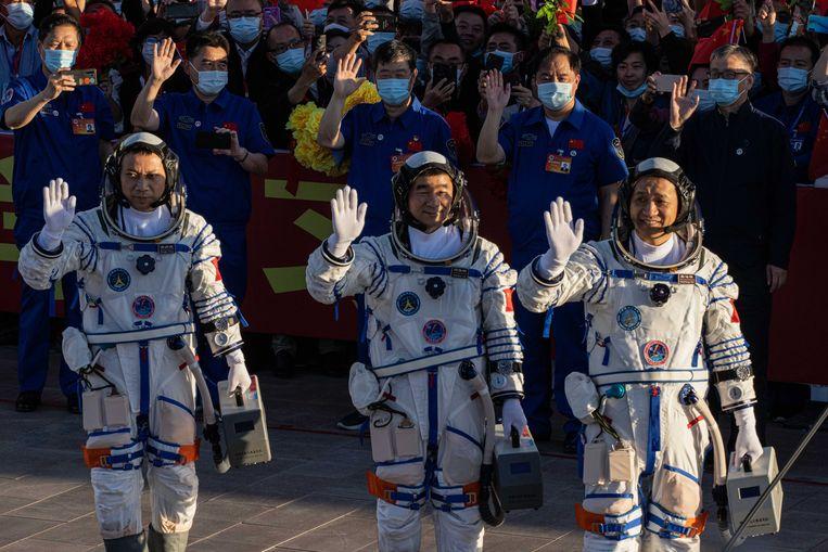 De Chinese astronauten Tang Hongbo, Nie Haisheng, en Liu Boming zwaaien tijdens een vertrekceremonie voorafgaande aan hun ruimtevlucht naar het Hemels Paleis 'Tiangong', het eerste echte ruimtestation van het land. Beeld EPA