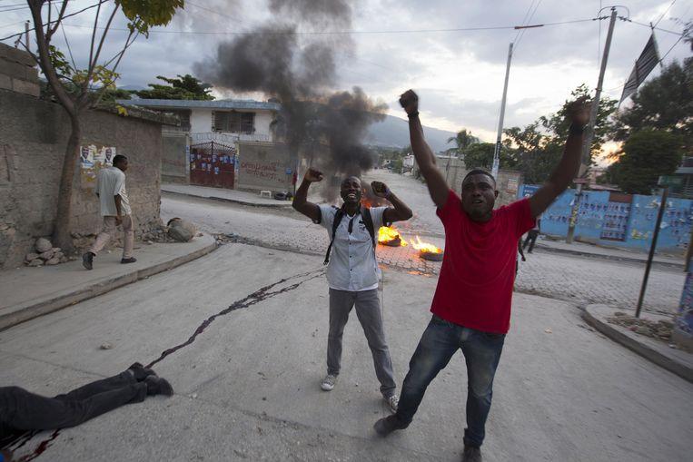 Een dood lichaam ligt op de grond terwijl supporters van presidentskandidaat Moise Jean-Charles slogans roepen nadat de officiële resultaten van de vekiezingen bekendgemaakt werden door de Provinicale Verkiezingsraad in de buurt van Delmas, Port-au-Prince, Haïti. Beeld ap