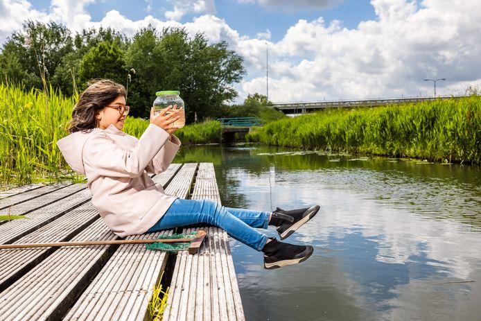 Een jonge onderzoekster van het project Vang de Watermonsters! bij een water in Barendrecht.