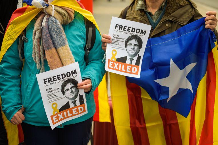 Betogers houden posters met de afbeelding van Carles Puigdemont vast tijdens een protestactie voor de gevangenis in Neumünster waar hij wordt vastgehouden. Beeld EPA
