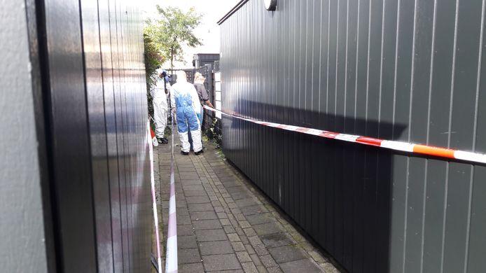 Inspecteurs aan het werk in het steegje achter de woning in Arnhem waar vrijdag een dode is gevonden.