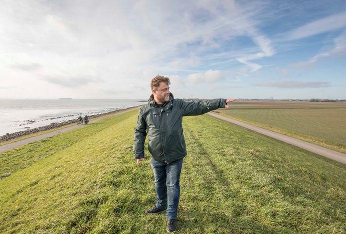 NIOZ-onderzoeker Jim van Belzen op de dijk bij Coudorpe. De Borsselepolder rechts ligt door bodemdaling lager dan de Westerschelde.