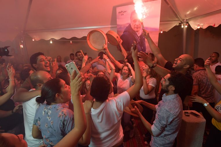 Aanhangers van presidentskandidaat Nabil Karoui vieren zondagavond feest voor zijn hoofdkantoor in Tunis. Beeld AFP