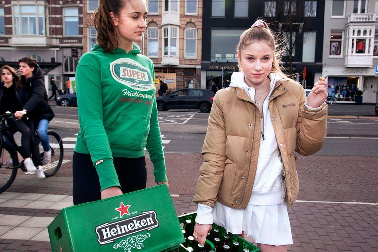 Vivian (17) en haar vriendin Sanne (16) kochten bier voor een huisfeestje. Vivian neemt direct de houding aan van een professioneel model. Beeld Martijn van de Griendt