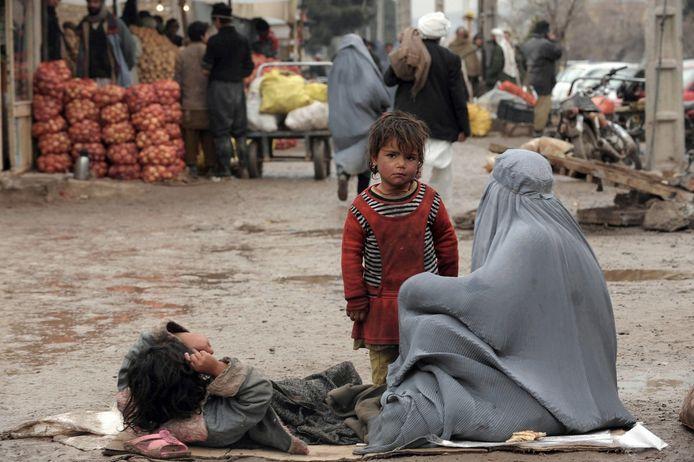 Een Afghaanse vrouw en haar kinderen bedelen in Herat.