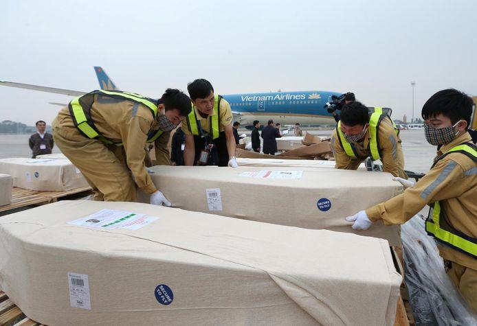 Medewerkers van het vliegveld in Hanoi halen de doodskisten uit het vliegtuig waarmee de stoffelijke overschotten werden vervoerd van Londen naar Vietnam.