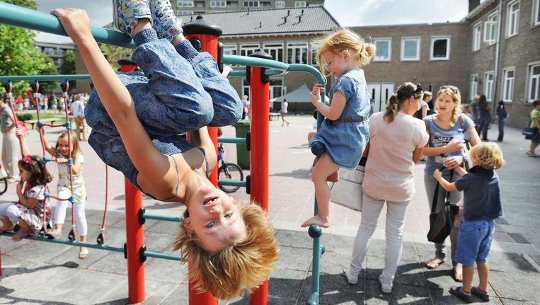 Kinderen spelen op het schoolplein en moeders nemen de dagelijkse problemen door. Beeld Guus Dubbelman / de Volkskrant