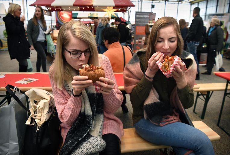 Vrouwen eten een plantaardige burger op de VeggieWorld Winterfair. Beeld Marcel van den Bergh / de Volkskrant