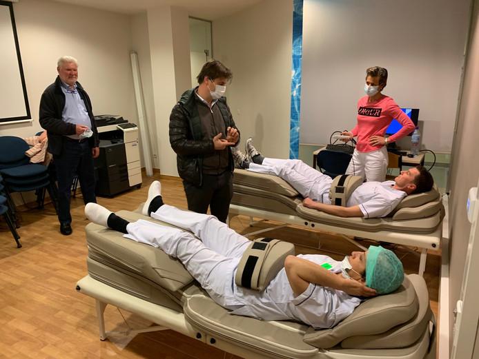 Zorgverleners testen de toestellen uit terwijl Yannick De Clercq (directeur netwerking en fundraising UZ Gent) en Gella Vande Caveye toekijken.