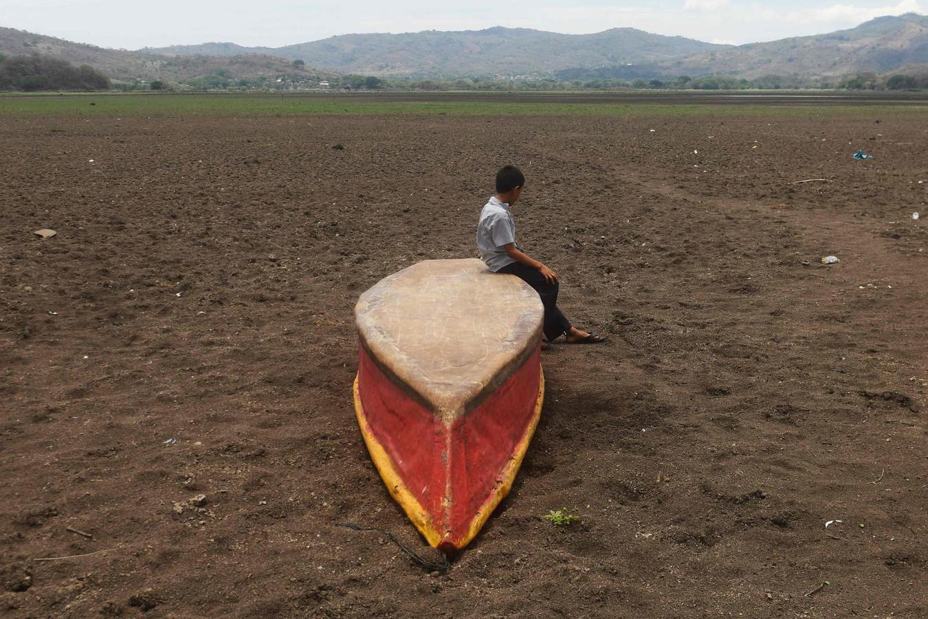 Een jongen op een verlaten bootje in het opgedroogde Atescatempa-meer in Guatemala.