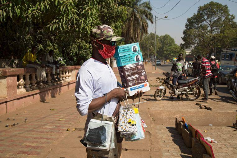 Een straatverkoper probeert mondkapjes te slijten in Bamako, Mali. Beeld AFP