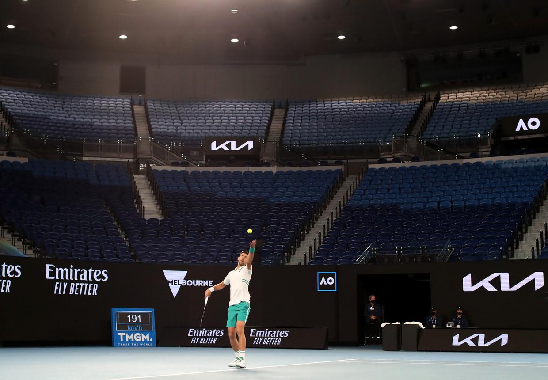 In een lege Rod Laver Arena serveert Novak Djokovic in zijn partij tegen Milos Raonic. Djokovic won in vier sets. Beeld REUTERS