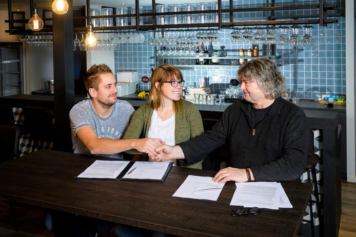 Eigenaren Youri Labee (links) en Amber Labee (midden) van Kom Aan Tafel! schudden PvdA-wethouder Ben van der Plas (rechts) de hand na het ondertekenen van de overeenkomst.