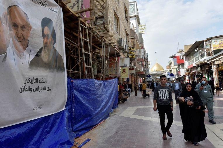 Een poster toont de paus en ayatollah Al-Sistani, de geestelijke leider van de sjiiten in Irak, in een straat in de stad Najaf. Beeld REUTERS