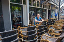 Paul van Boxtel, eigenaar van Café Thomas en Café de Spijker bij zijn nog opgestapelde terrasmeubilair.