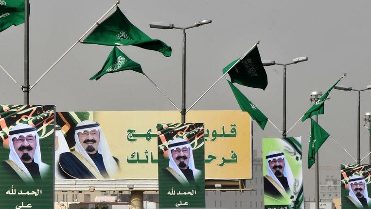 Foto's van koning Abdoellah hangen naast wapperende Saoedische vlaggen langs de weg in hoofdstad Riyadh. Beeld AFP