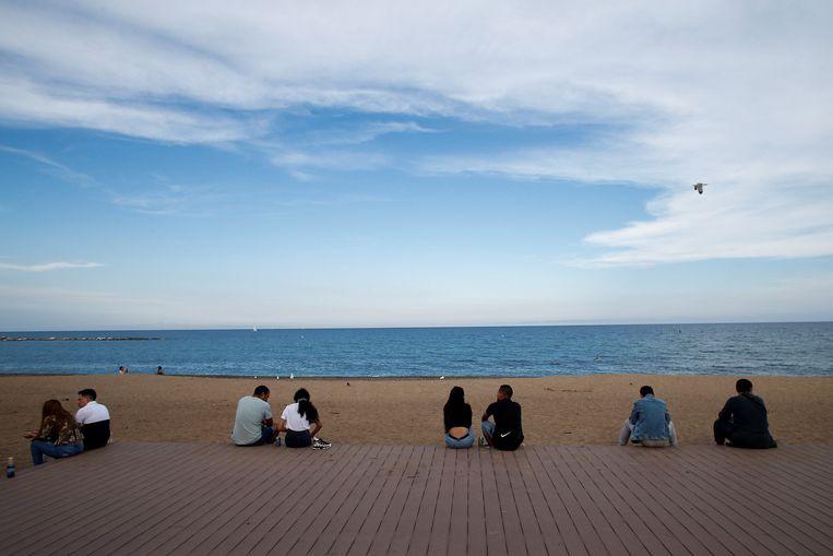 Mensen respecteren de social distance terwijl ze genieten van het strand in Barcelona. Beeld EPA