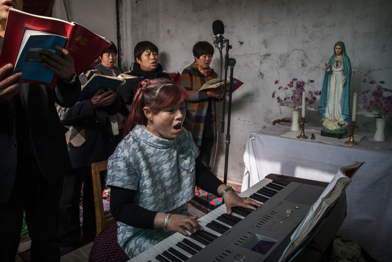Een Chinese katholieke vrouw speelt op een keyboard terwijl ze liedereen zingt in de Palmzondagmis tijdens de Paasweek in een 'ondergrondse' of 'onofficiële' kerk. Beeld Getty Images