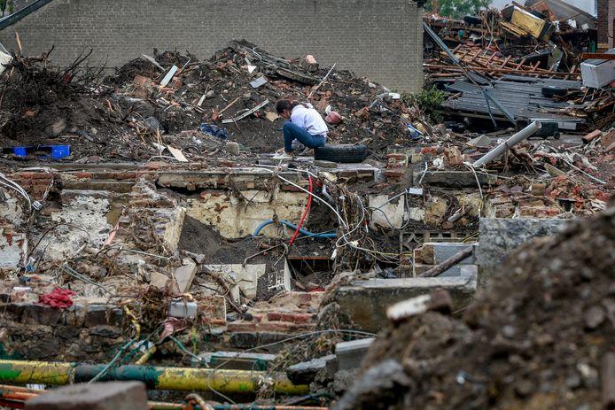 Een vrouw zit tussen de ruïnes van verwoeste huizen in Pepinster.