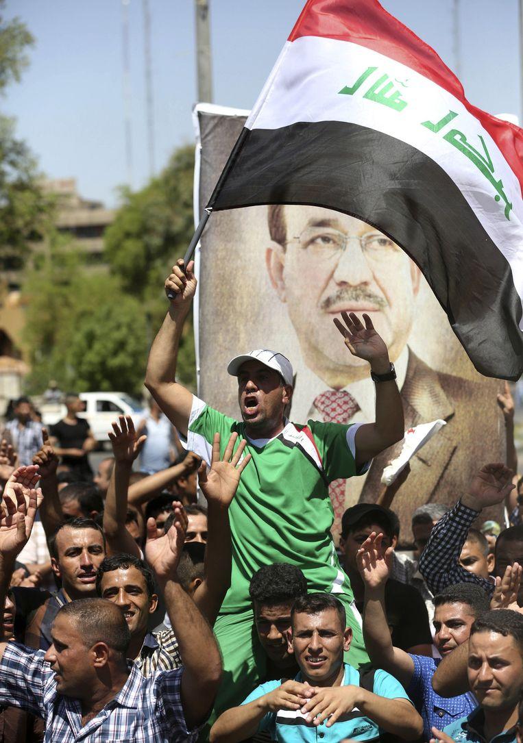 Mensen laten vandaag zien Al-Maliki te steunen in Bagdad met vlaggen en posters van de premier. Beeld AP