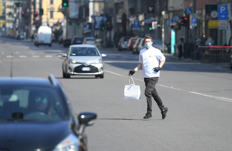 Een man met beschermend mondmasker en handschoenen in de straten van Milaan.